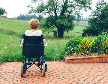 woman in wheelchair looking at field and trees, Link to Designing Environments for Memory Care Residents Part 3 article