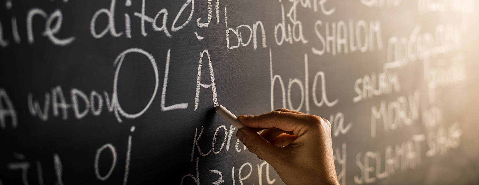 Hand writing at chalkboard in multiple languages