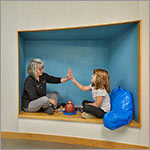 Teacher and child in cubby in wall, link to larger image